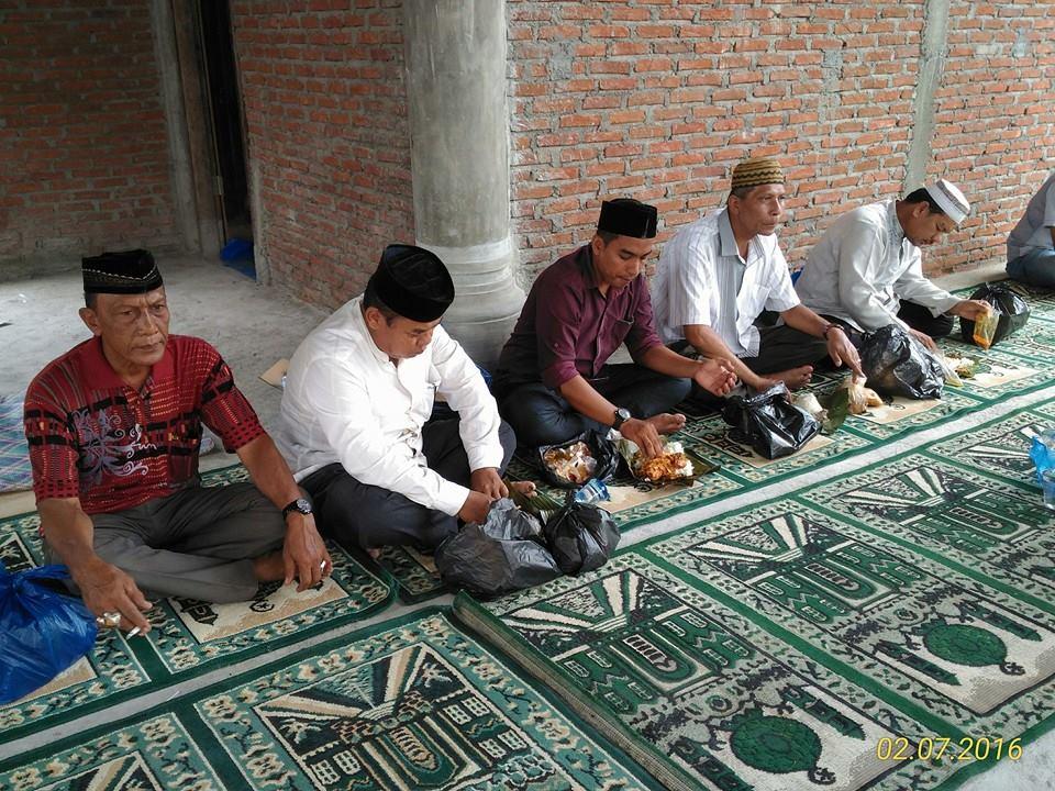 Keuchik/Kades Rizky (tengah) Sedang Menyantap Hidangan Maulid (Shafwandi)