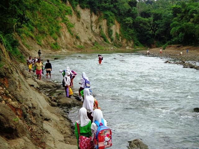 Puluhan siswa menyeberangi sungai hendak berangkat sekolah.
