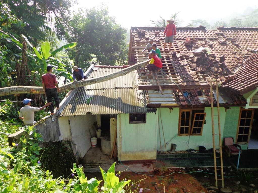 Rumah milik Turmudi (58) sedang diperbaiki warga usai tertimpa pohon, Minggu (6/3) kemarin